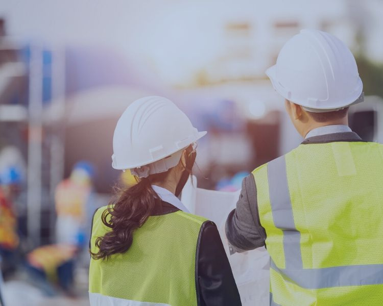 Man and a woman in high vis vests and hard hats