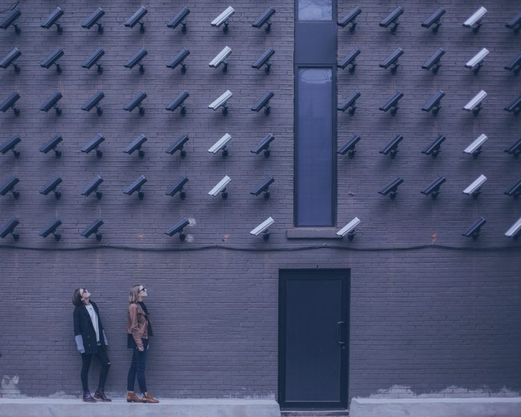 Two women looking up in front of a wall of security cameras